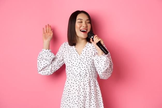 Gelukkige aziatische vrouw die in de microfoon zingt, plezier heeft in de karaokebar, staande over een roze achtergrond. ruimte kopiëren
