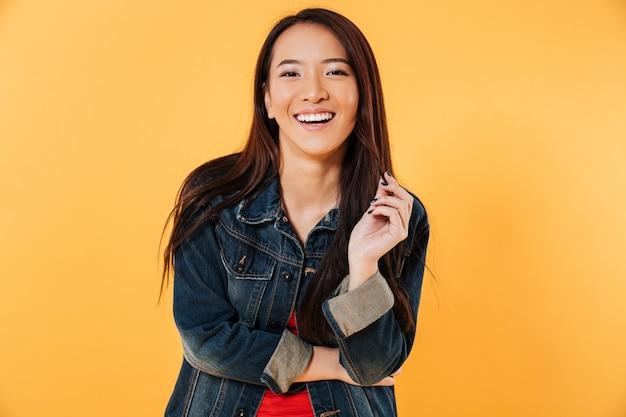 Gelukkige aziatische vrouw die in denimjasje haar haar houdt