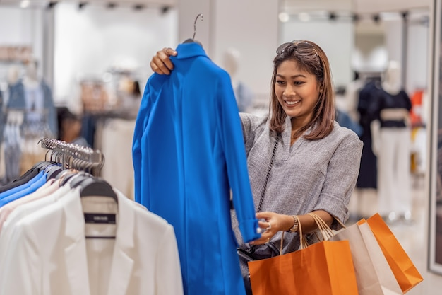 Gelukkige aziatische vrouw die kleren in winkelopslag kiezen met gelukkige actie op afdelingscentrum