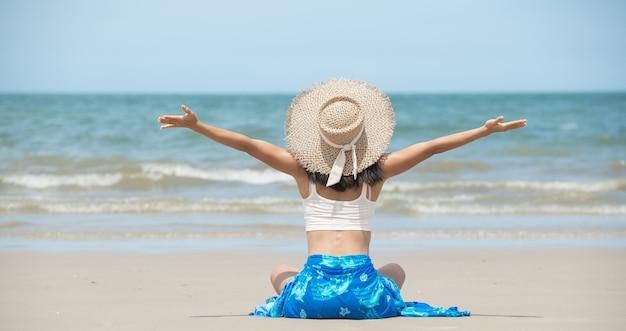 Gelukkige aziatische vrouw die lacht en plezier heeft op het strand