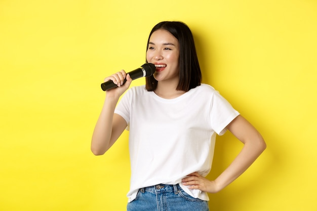Gelukkige aziatische vrouw die lied zingt in karaoke, microfoon vasthoudt en opzij kijkt met een vrolijke glimlach, staande over gele achtergrond.