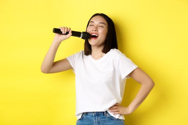 Gelukkige aziatische vrouw die lied zingt in karaoke, microfoon vasthoudt, over gele achtergrond staat