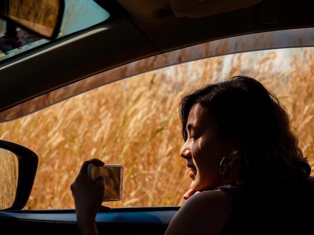 Gelukkige aziatische vrouw die met de auto reist. mooie vrouwelijke reizigers genieten en glimlachen terwijl ze video's van reizen opnemen of foto's maken van het uitzicht buiten door smartphoneweergave vanuit de auto.