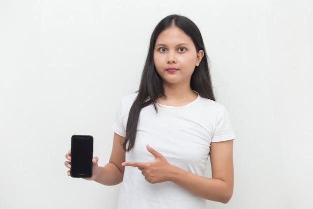 Gelukkige aziatische vrouw die mobiele celtelefoon aantoont portret van het glimlachen meisje die zich voordeed op witte achtergrond