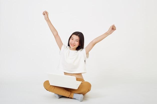 Gelukkige aziatische vrouw die op laptopcomputer werkt terwijl ze op de vloer zit met gekruiste benen geïsoleerd over witte achtergrond, terug naar schoolconcept