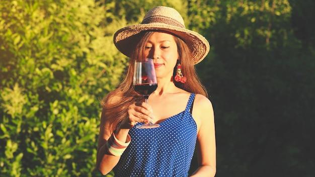 Gelukkige aziatische vrouw die rode wijn drinkt, vieringsconcept