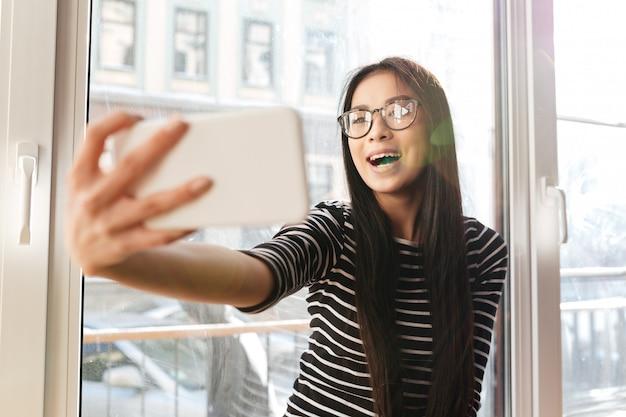 Gelukkige aziatische vrouw die selfie op vensterbank maken