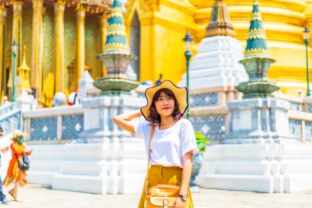 Gelukkige aziatische vrouw die tempel in thailand bezoekt