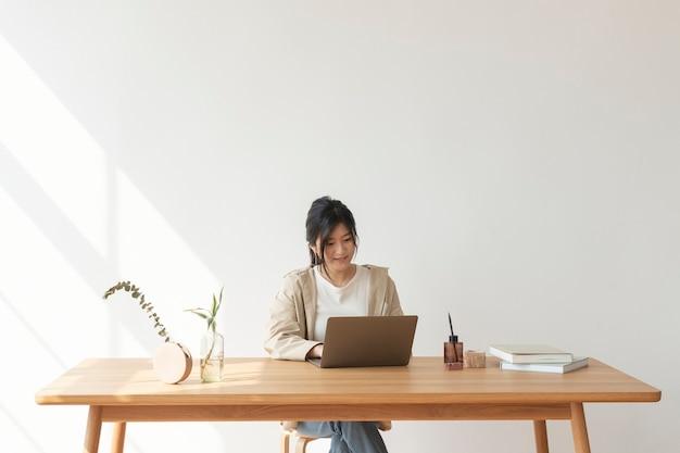 Gelukkige aziatische vrouw die vanuit huis werkt