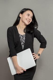 Gelukkige aziatische vrouw die zich voordeed met laptop terwijl ze omhoog keek