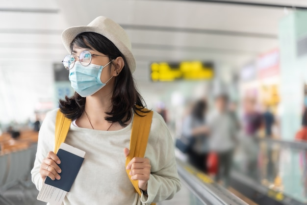 Gelukkige aziatische vrouw draagt beschermend gezichtsmasker en bril wandelen in internationale luchthaventerminal tijdens viruspandemie.