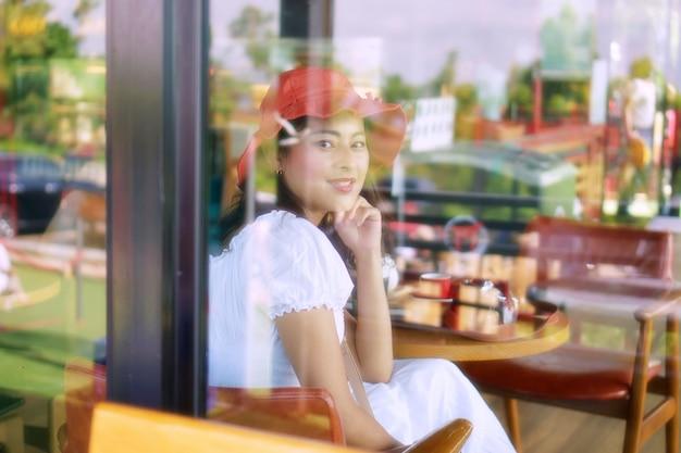 Gelukkige aziatische vrouw glimlacht en kijkt door vensterglas, aziatisch meisje ontspant in café