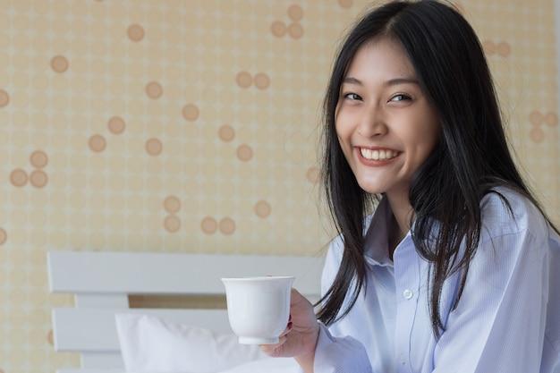 Gelukkige aziatische vrouw het drinken koffie op bed