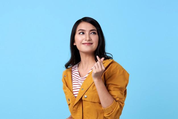 Gelukkige aziatische vrouw in geel overhemd en handgebaar minihart over blauwe ruimte.