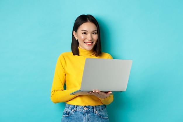 Gelukkige aziatische vrouw in gele trui met behulp van laptop, online winkelen of werken, permanent over blauwe achtergrond.