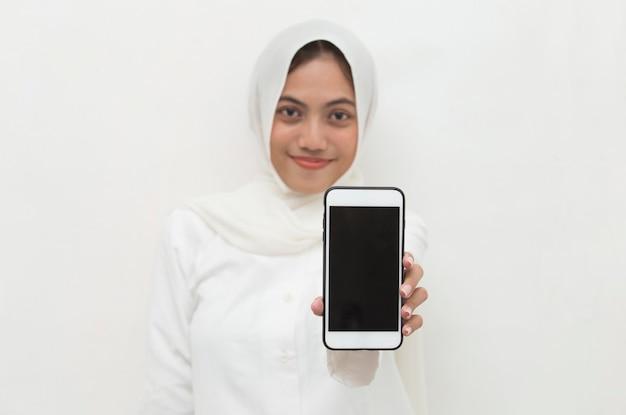 Gelukkige aziatische vrouw in hijab die mobiele celtelefoon demonstreren portret van glimlachend meisje