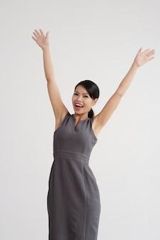 Gelukkige aziatische vrouw in kleding het stellen binnen met haar handen omhoog in lucht