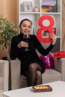 Gelukkige aziatische vrouw in zwarte jurk zittend op een stoel met een glas wijn met nummer acht glimlachend vrolijk in lichte woonkamer vieren internationale vrouwendag maart