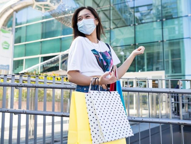 Gelukkige aziatische vrouw met het winkelen masker