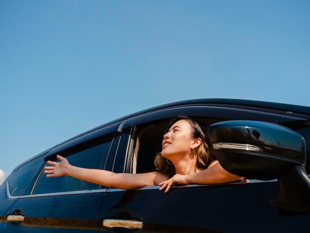 Gelukkige aziatische vrouw met kort haar die een hand opsteekt tegen de wind tijdens het reizen met de auto. aantrekkelijke vrouwelijke reizigers genieten en glimlachen naar het uitzicht buiten de auto, op de lokale weg, zomer.