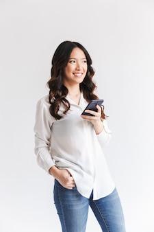 Gelukkige aziatische vrouw met lang donker haar die zwarte mobiele telefoon houden en opzij kijken
