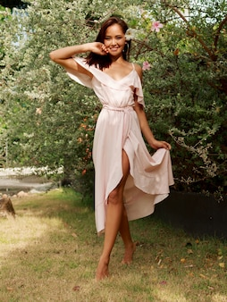 Gelukkige aziatische vrouw met spontane glimlach in het roze kleding stellen in de zomertuin