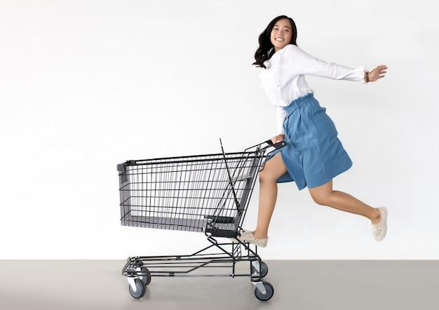 Gelukkige aziatische vrouw met winkelwagentje klaar om te winkelen
