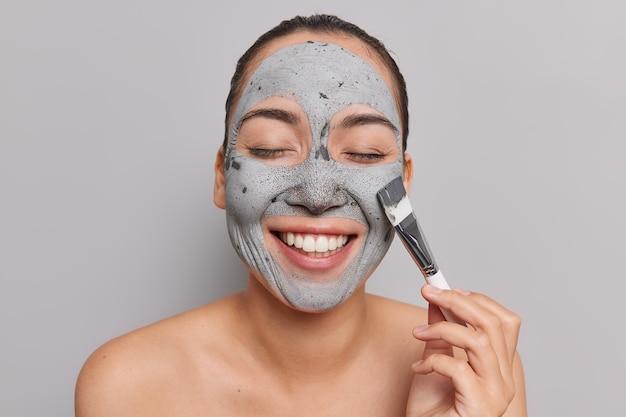 Gelukkige aziatische vrouw ontvangt cosmetisch masker en gebruikt een brede glimlach
