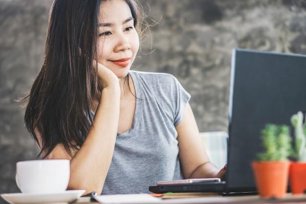 Gelukkige aziatische vrouwelijke freelancer werkt vanuit kantoor aan huis