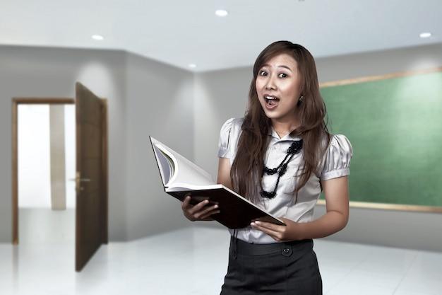 Gelukkige aziatische vrouwelijke leraar klaar om te onderwijzen
