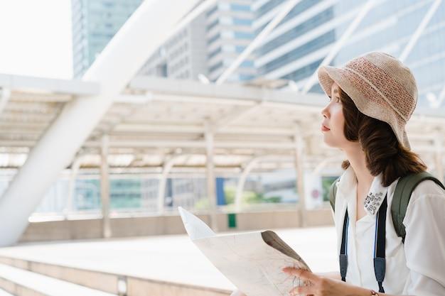 Gelukkige aziatische vrouwelijke reiziger, toeristische zwerver met trendy look die richting zoekt op de locatiekaart terwijl hij in de zomer naar het buitenland reist
