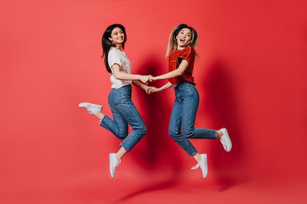 Gelukkige aziatische vrouwen die in modieuze t-shirts en jeansbroeken op geïsoleerde muur springen