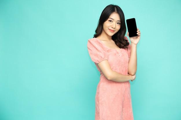 Gelukkige aziatische vrouwenglimlach en het houden van mobiele telefoon die over lichtgroene achtergrond wordt geïsoleerd