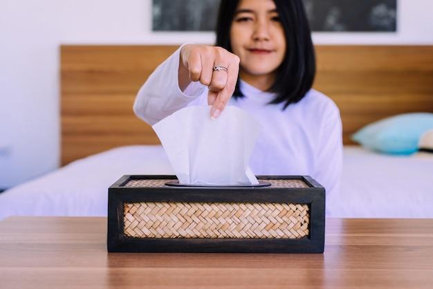 Gelukkige aziatische vrouwenhanden die wit papieren zakdoekje van houten vakje trekken