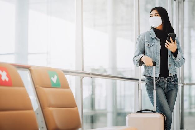 Gelukkige aziatische vrouwenreiziger die masker draagt ter bescherming tegen coronavirus met smartphone die zich met bagage naast sociale afstandsstoel bevindt
