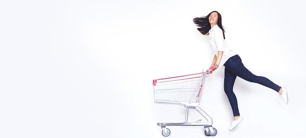 Gelukkige aziatische vrouwensprong met boodschappenwagentje
