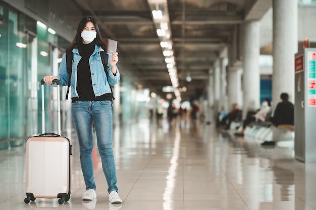 Gelukkige aziatische vrouwentoerist die de holdingspaspoort van het gezichtsmasker dragen