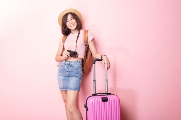 Gelukkige aziatische vrouwentoerist op roze muur