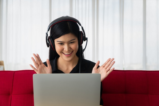 Gelukkige aziatische vrouwenzitting op een bank en een videoconferentie met een partner