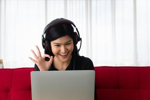 Gelukkige aziatische vrouwenzitting op een bank en videoconferentie met een zakenpartner