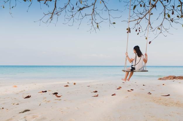 Gelukkige aziatische vrouwenzitting op een schommeling op het witte zand