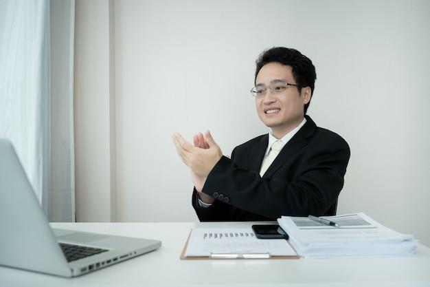Gelukkige aziatische zakenman die een online videoconferentie maakt terwijl hij thuis werkt. aziatische jonge ceo klappen na het beëindigen van de online vergadering. werk vanuit huis concept.