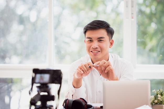 Gelukkige aziatische zakenman die videoblog doen