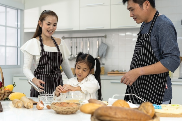 Gelukkige azië-familie met dochter die deeg maakt om koekjes te bakken, dochter helpt ouder bij het voorbereiden van het bakgezinsconcept