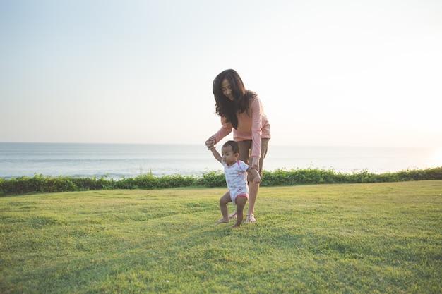 Gelukkige baby die zijn eerste stappen op een groen gras maakt