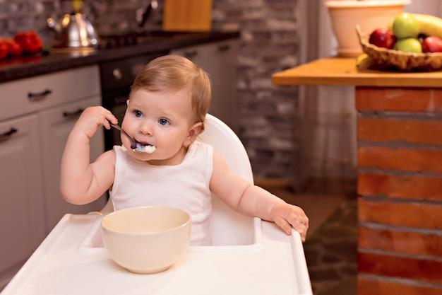 Gelukkige baby eet melkpap met een lepel. portret van een gelukkig meisje in een kinderstoel in de keuken
