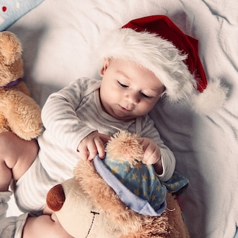 Gelukkige baby in de hoed van de kerstman met zacht speelgoed. het concept van kerstmis