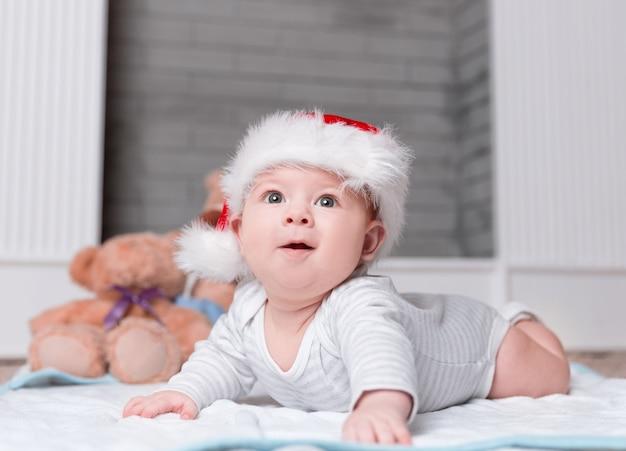 Gelukkige baby in de hoed van de kerstman op kerstavond. het concept van kerstmis