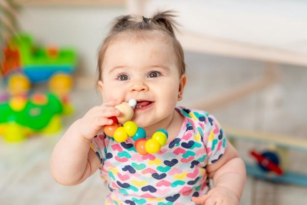 Gelukkige baby met een stuk speelgoed thuis of in de kleuterschool