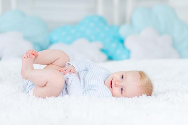 Gelukkige baby op het bed op zijn rug glimlachen, blonde zes maanden oud van de babyjongen